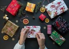 妇女手在黑木桌上的礼物盒做弓在其他礼物附近 圣诞节新年度 免版税库存照片