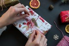 妇女手在黑桌上的礼物做弓 免版税库存照片