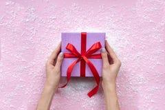 妇女手平的位置拿着礼物的被包裹 在雪的礼品 桃红色背景 免版税库存图片