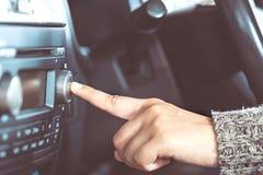 妇女手打开收音机,当驾驶汽车时 免版税库存照片
