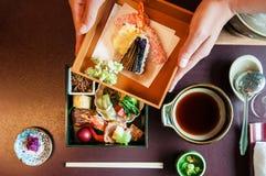 妇女手打开日本人Bento用烤海鲜和天麸罗 免版税库存照片