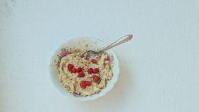 妇女手投入碗用燕麦粥和野草莓 影视素材