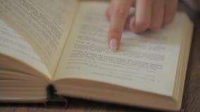 妇女手拿着一本书并且移动她的沿页的手指,当读教育休闲读书纸时 股票录像
