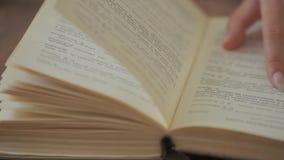 妇女手拿着一本书并且移动她的沿页的手指,当读教育休闲读书纸时 股票视频