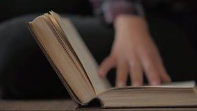 妇女手拿着一本书并且移动她的沿页的手指,当读教育休闲读书纸时 影视素材