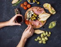 妇女手拿着一杯酒 开胃菜,意大利开胃小菜,火腿,橄榄,乳酪,面包,葡萄,在黑暗的石背景的梨 免版税库存照片