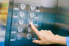 妇女手指新闻在电梯的数字地板 免版税库存照片