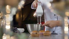 妇女手接近的射击混合在碗的白鸡蛋奶油使用马达搅拌器 股票录像