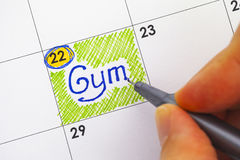 妇女手文字在日历的提示健身房 库存图片
