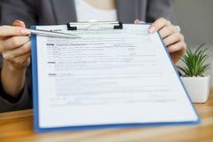妇女手文字或签字在文件 免版税库存照片