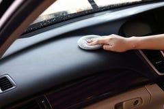 妇女手清洁皮革在汽车的黑色控制台 库存图片