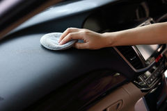 妇女手清洁皮革在汽车的黑色控制台 免版税库存照片