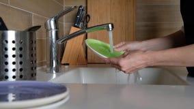 妇女手漂洗板材在厨房水槽-在家做差事 盘洗涤物惯例,静态照相机 ?? 影视素材