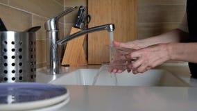妇女手漂洗玻璃在厨房水槽-在家做差事 盘洗涤物惯例,静态照相机 ?? 股票视频