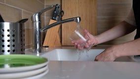 妇女手漂洗玻璃在厨房水槽-在家做差事 盘洗涤物惯例,静态照相机 ?? 股票录像