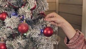 妇女手特写镜头装饰圣诞树的由红色球 股票视频