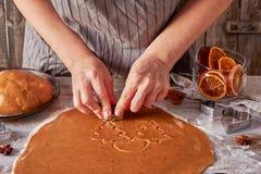 妇女手由滚动的姜饼面团做曲奇饼形状 免版税图库摄影