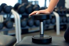妇女手的关闭有在长凳的哑铃的在健身房 库存图片