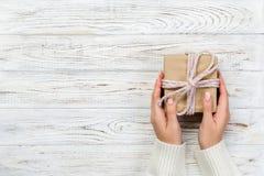 妇女手给被包裹的华伦泰或其他假日手工制造礼物在纸与桃红色丝带 当前箱子,礼物的装饰 库存照片