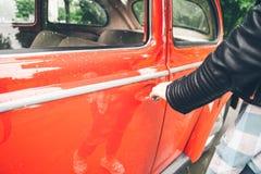 妇女手老减速火箭的汽车的开门 免版税库存照片