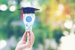 妇女手藏品嵌齿轮里面在与毕业生帽子的电灯泡在自然绿色背景、教育和创造性的想法和 库存照片