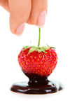 妇女手藏品巧克力浸洗了草莓 免版税库存照片