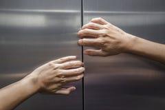妇女手设法停止闭合的电梯的门 免版税库存图片