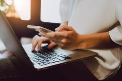 妇女手软的焦点与在书桌上的电话一起使用在咖啡店 葡萄酒口气 免版税库存照片