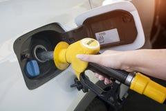 妇女手重新装满的和抽的汽油上油有燃料的汽车在他加油驻地、产业或者运输概念 库存图片