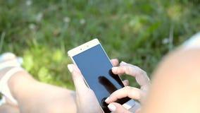 妇女手键入在电话的消息,送sms,电子邮件 股票录像