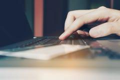 妇女手键入的键盘膝上型计算机和信用卡与购物 免版税库存图片