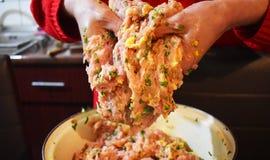 妇女手miced新鲜的肉为丸子做准备 手工混合肉与鸡蛋、荷兰芹和大蒜 免版税库存图片