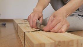 妇女打开一个木机架,买在商店,裁减有刀子的包装的磁带 有刀子特写镜头的手 影视素材