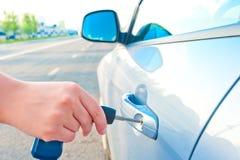 妇女打开一辆新的汽车的门钥匙 免版税库存照片