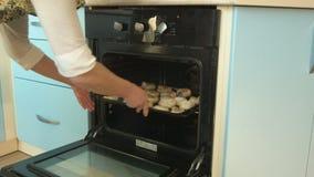 妇女打开了电烤箱,采取了盘子用面团 我在烤箱投入了它并且油煎了它并且结束了它 股票录像
