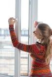 妇女打开塑料窗口 免版税库存图片