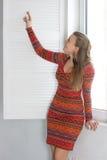 妇女打开塑料窗口 免版税图库摄影