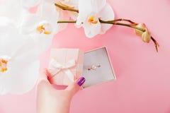 妇女打开有一个银色珍珠圆环的一个礼物盒围拢与兰花 建议 库存照片