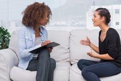 妇女打手势和谈话与她的治疗师 库存照片