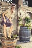 妇女打碎葡萄,收割期 免版税库存照片