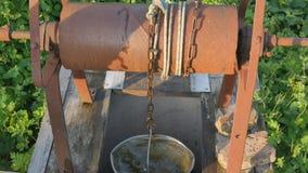 妇女投下与桶的链子入土气井挑水 葡萄酒水井链子关闭 老生锈的链子  股票视频