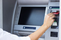 妇女投入了她的信用卡在ATM 库存图片