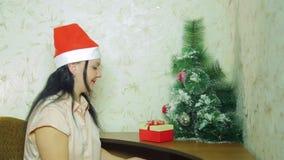 妇女投入家庭的圣诞礼物在圣诞树下 股票录像