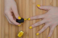 妇女投入黄色指甲油 免版税图库摄影