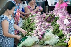 妇女投掷的出售莲花入在磨擦Bua节日的小船, 库存照片