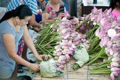妇女投掷的出售莲花入在磨擦Bua节日的小船, 免版税库存图片