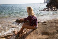 妇女投掷的石头到海里 免版税库存照片