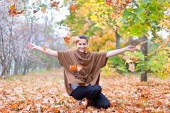 妇女投掷秋叶 免版税库存图片