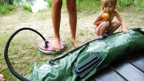 妇女抽有脚踏泵的一条可膨胀的小船 影视素材