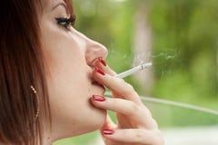 妇女抽烟的香烟。 免版税库存图片